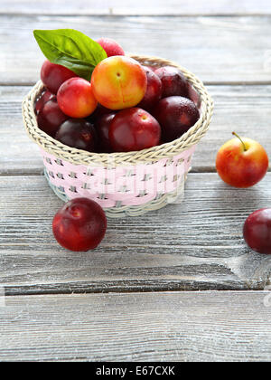 wicker basket full of ripe plums, food closeup - Stock Photo