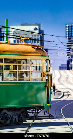 Classic green heritage iconic Melbourne tram approaching wavy tramlines city centre, Melbourne, Australia - Stock Photo