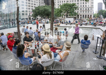 group sitting at round table socializing eating takeout lunch & drinking cokes on plaza among people thronging midtown - Stock Photo