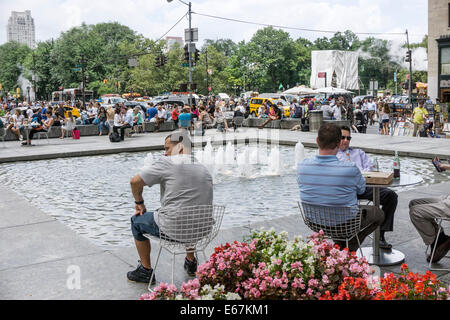 people sit relaxing next to pool & fountain at General Motors Plaza with view of crowds thronging Fifth Avenue sidewalks - Stock Photo