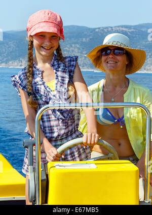 Mother with her daughter in a motorboat on sea promenade. - Stock Photo