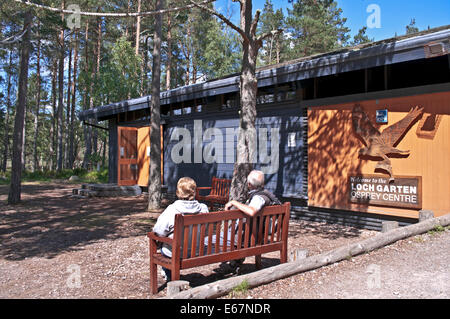 Two visitors sitting on bench at RSPB Loch Garten Osprey Centre, Abernethy Forest National Nature Reserve, Cairngorms, - Stock Photo
