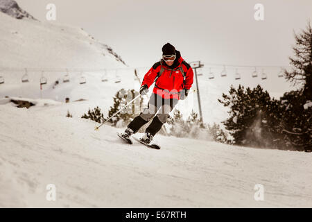 Skier wearing a woollen hat, goggles and red jacket, speeds down the piste. - Stock Photo