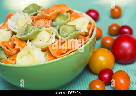 Tortellini, Tricolor, Green Orange Colored Pasta in a Bowl - Stock Photo
