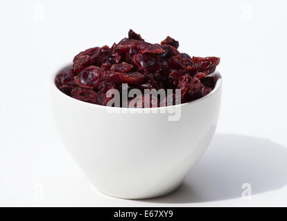 Dried cranberries in a white bowl on white background - Stock Photo