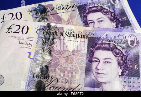 Two English Bank of England Twenty Pound notes on blue background - Stock Photo