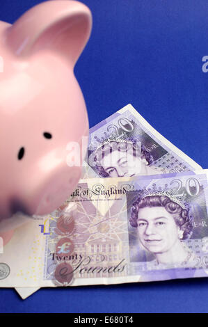 Two English Bank of England Twenty Pound notes on blue background with pink piggy bank. Vertical. - Stock Photo