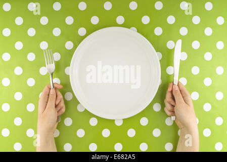 Female hands at dinner table holding fork and a knife above empty flat white plate, dieting concept. - Stock Photo