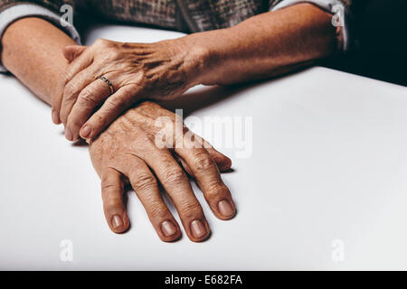 Close-up image of senior woman sitting by a table with focus on her hands. Old female hands on a desk. - Stock Photo