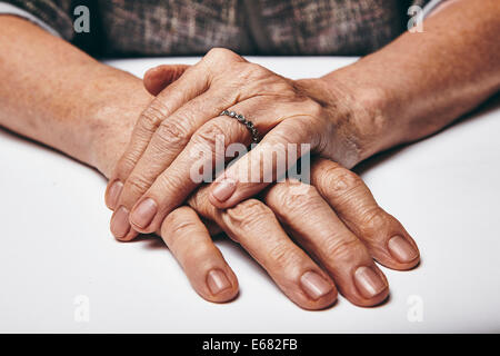 Macro of an old lady sitting with her hands clasped on a table. Elderly woman's hands with a ring resting on grey - Stock Photo