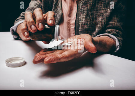Cropped shot of a old woman sitting at a table shaking a pill out of a pill bottle. Focus on hands. Senior female - Stock Photo