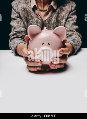 Cropped studio shot of senior female hands holding a coin bank while sitting at a table. Old woman holding a piggybank. - Stock Photo