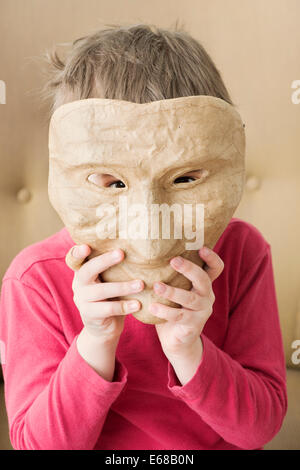 Sad little girl hiding face behind happy mask - Stock Photo