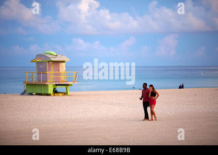 Miami in Florida USA a couple in love walk along the beach at dawn passing a lifeguard tower - Stock Photo