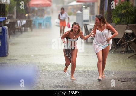 Two woman enjoying running in the rain - Stock Photo