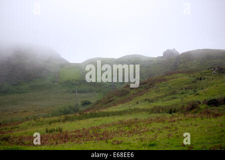 A lone house stands on a hillside, looking out over the Northern Irish moors of Rathlin Island. A low lying cloud - Stock Photo