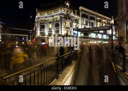 A composite image enhances the busy feel of Oxford Circus station as commuters travel through London. The movement - Stock Photo