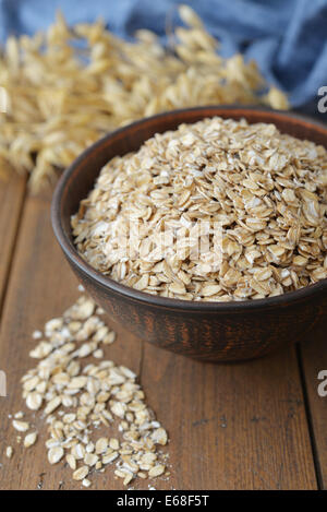 Oatflakes in a bowl on wooden background - Stock Photo