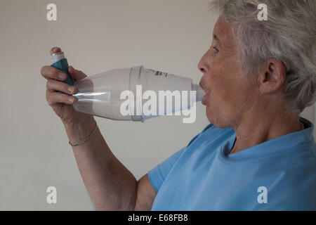 Elderly asthmatic woman using a Volumatic spacer device for Ventolin inhaling - Stock Photo