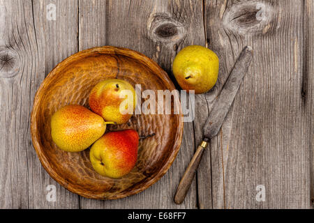 Pears on a wooden plate with a knife on an old rustic wooden table in country style - Stock Photo