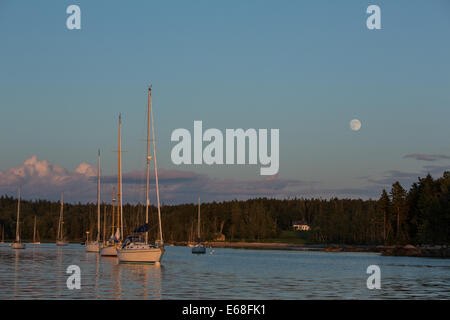Center Harbor, Brooklin, Maine - 9 August 2014. The nearly full moon rising over Center Harbor at sunset. - Stock Photo