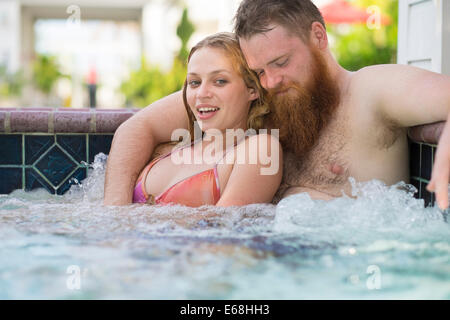 Young woman and bearded man enjoying a bath in a hot tub pool. - Stock Photo