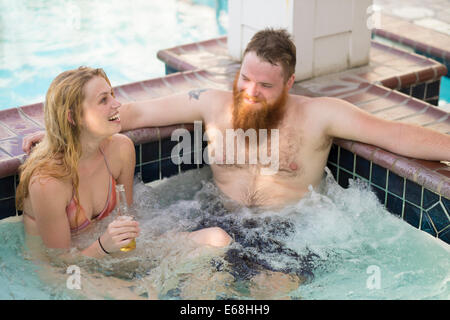 Jacuzzi in wellness area of hotel with young adults drinking beer and laughing. - Stock Photo