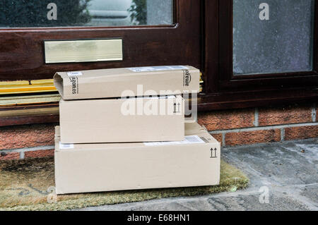 A number of Amazon cardboard boxes left outside a house front door. - Stock Photo