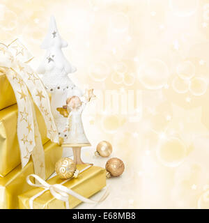 Golden wrapped christmas presents with an white angel on wooden background. - Stock Photo