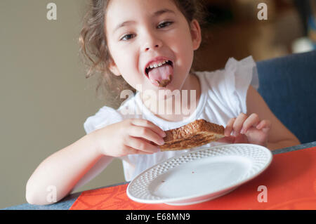 Child eating bread with chocolate spread - Stock Photo