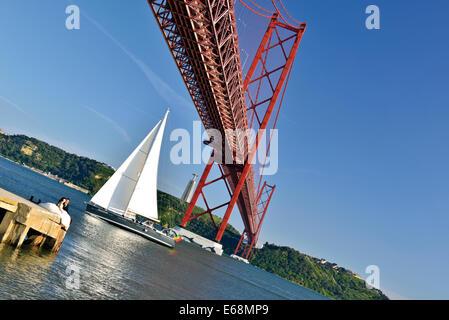 Portugal, Lisbon: Sailing boat crossing the bridge Ponte 25 de Abril - Stock Photo