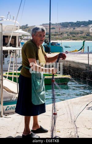 Woman sortting fishing nets on the quayside, Marsaxlokk, Malta. - Stock Photo