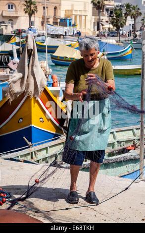 Woman sorting fishing nets on the quayside, Marsaxlokk, Malta. - Stock Photo