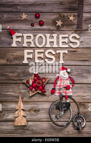 Merry Christmas 'Frohes Fest' in german letters. Greeting card with wood, red and white. - Stock Photo