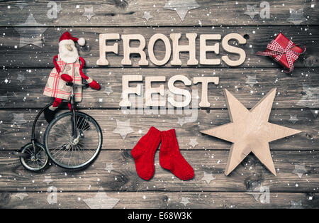 Merry christmas greeting card with german text plus red santa and wooden handmade decoration. - Stock Photo