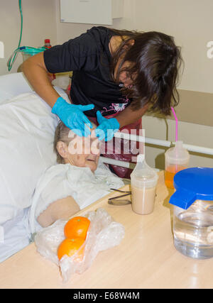 Elderly patient in her nineties diagnosed with cancer having face cream applied by relative in NHS hospital. England. - Stock Photo