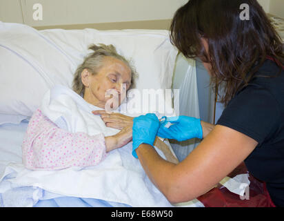Elderly patient in her nineties diagnosed with cancer having nails cut by relative in NHS hospital. England. UK - Stock Photo