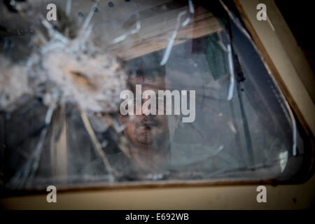 Makhmour, Northern Iraq. 18th Aug, 2014. Portrait of a Peshmerga soldier as seen behind the door of an American - Stock Photo