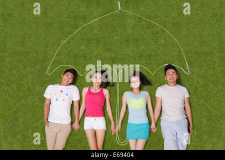Young people lying on grass under an artificial umbrella - Stock Photo