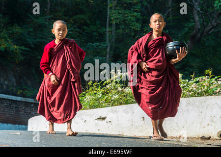 Young Buddhist novices with begging bowls collecting alms in the morning, Sagaing, Sagaing Region, Myanmar - Stock Photo