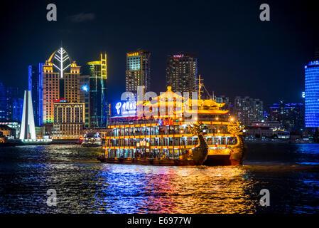 Illuminated dragon boat, pleasure boat on Huangpo, from The Bund, Hyatt at The Bund at the back, at night, Shanghai, - Stock Photo