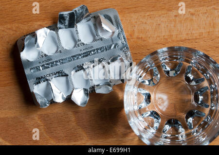 Empty packet of paracetamol tablets and glass of water on bedside table, viewed from above. - Stock Photo