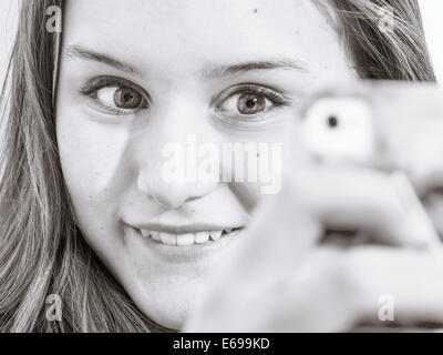 Caucasian teenage girl taking picture with cell phone - Stock Photo