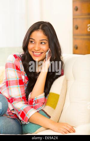 Hispanic woman talking on cell phone on sofa