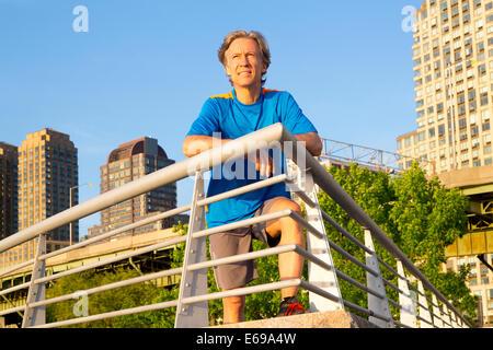 Caucasian man leaning on railing in urban park