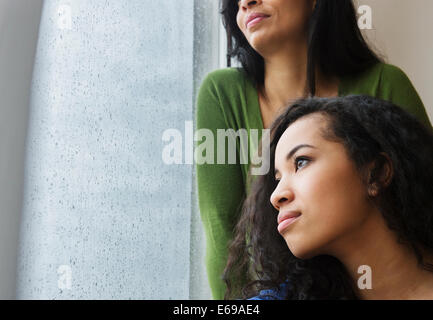 Mother and daughter daydreaming at window