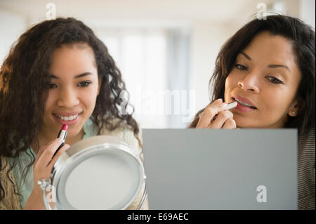 Mother and daughter applying makeup - Stock Photo