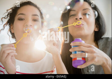 Mother and daughter blowing bubbles together
