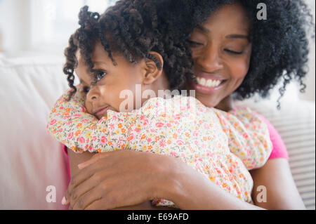 Mother hugging daughter on sofa - Stock Photo