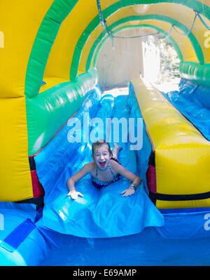 Caucasian girl laughing on water slide